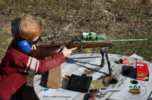 A five-year-old boy getting into a position to fire his Savage Cub T. This well-designed .22 rifle, with Savage's AccuTrigger, is ideal for training children.