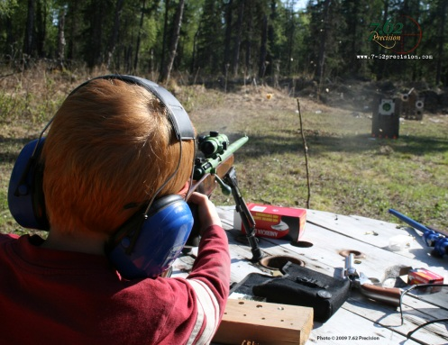 Apple Fragments fly as a six-year-old launches a bullet from a Savage Cub .22 rifle. Targets that react to a hit keep shooting fun for children.